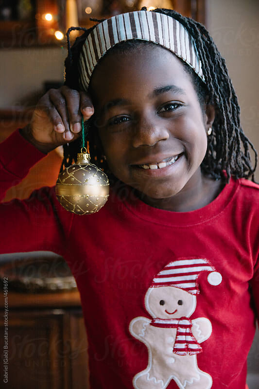 Black girl in ginger bread red pajama holding a Christmas decoration by Gabriel (Gabi) Bucataru for Stocksy United