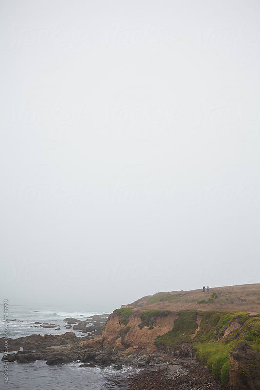 Two people walking along a beach trail with rocky coastline. by Robert Zaleski for Stocksy United