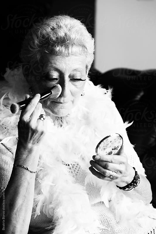 Senior woman putting face powder to her face by Beatrix Boros for Stocksy United