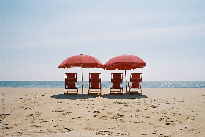 Four red beach chairs sit under two umbrellas in the summer sun looking out over the Atlantic ocean by Joey Pasco for Stocksy United