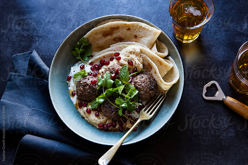 Spicy meatballs with pomegranate and mint hummus. Served with flat bread by Nadine Greeff for Stocksy United