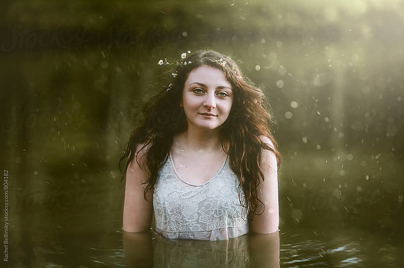A young woman with flowers in her hair stands chest deep in still pond waters by Rachel Bellinsky for Stocksy United