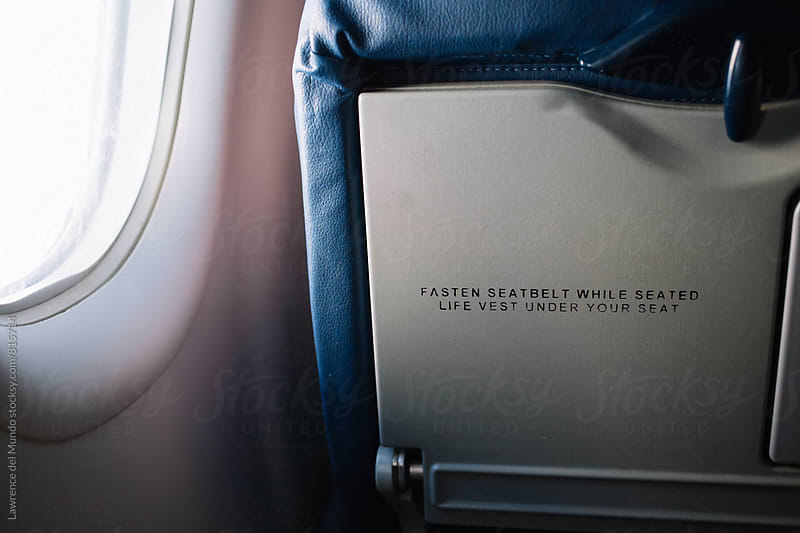 Friendly safety reminder at the back of an airplane seat by Lawrence del Mundo for Stocksy United