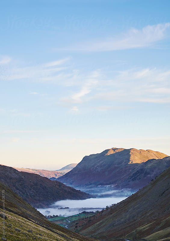 Fog formed in the valley at sunrise. Kirkstone Pass, Cumbria, UK. by Liam Grant for Stocksy United