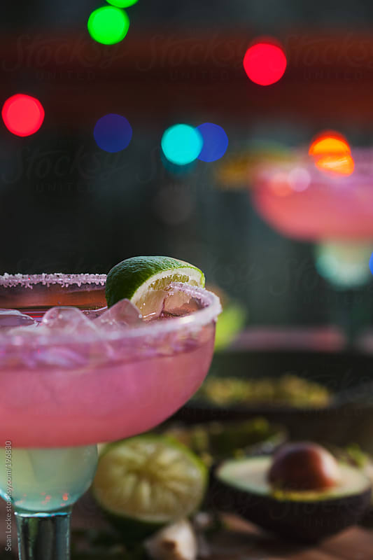 Fiesta: Focus On Margarita Glass With Avacado And Limes Behind by Sean Locke for Stocksy United