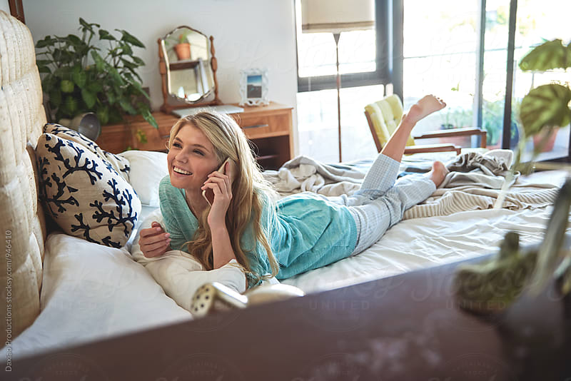 Pretty blonde woman talking on the phone lying on her bed  by Daxiao Productions for Stocksy United