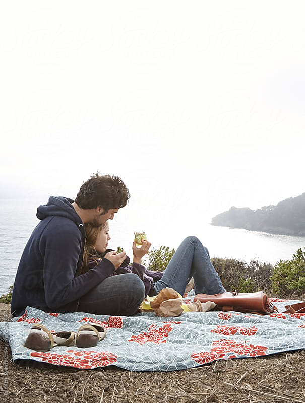 Couple having a picnic lunch on a cliff overlooking the ocean  by Trinette Reed for Stocksy United
