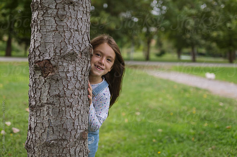 Girl peeking behind tree by Dejan Ristovski for Stocksy United