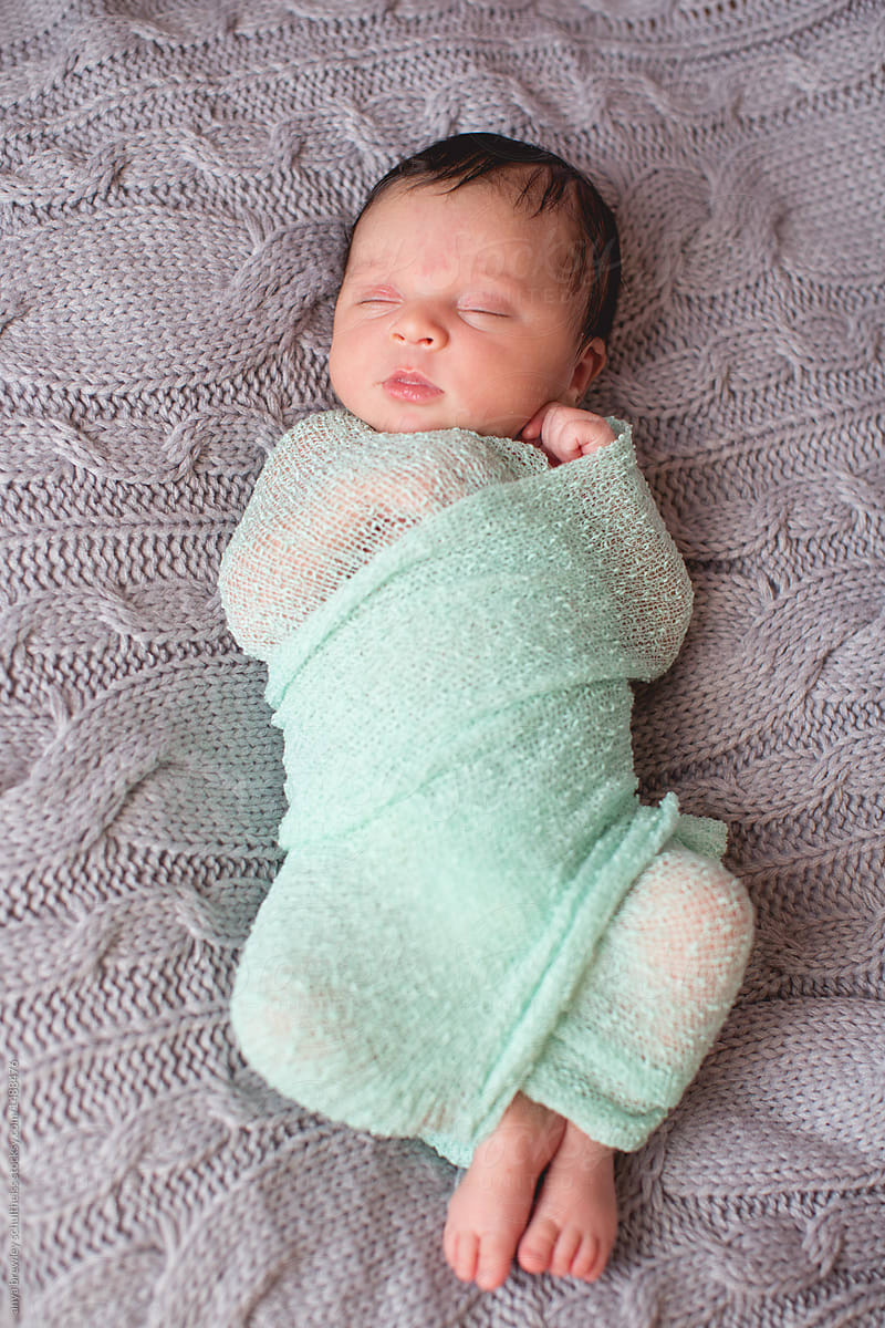 Newborn Baby Wrapped Up In Swaddling Blanket Sleeping Serenely