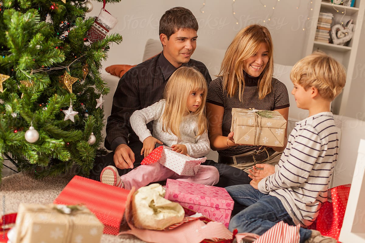 Happy Family Opening Christmas Gifts At Home | Stocksy United
