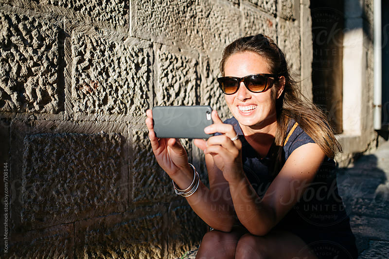 Attractive woman taking a photo with her mobile device  by Koen Meershoek for Stocksy United