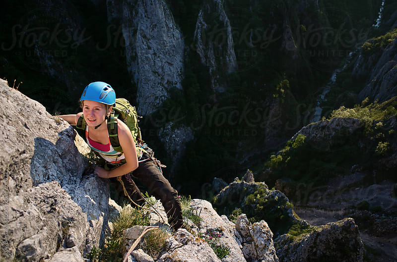 Young woman rock climbing high above the ground by RG&B Images for Stocksy United