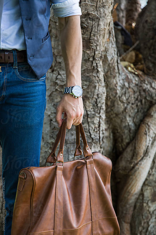 Fashionable young man holding brown bag by Jovo Jovanovic for Stocksy United