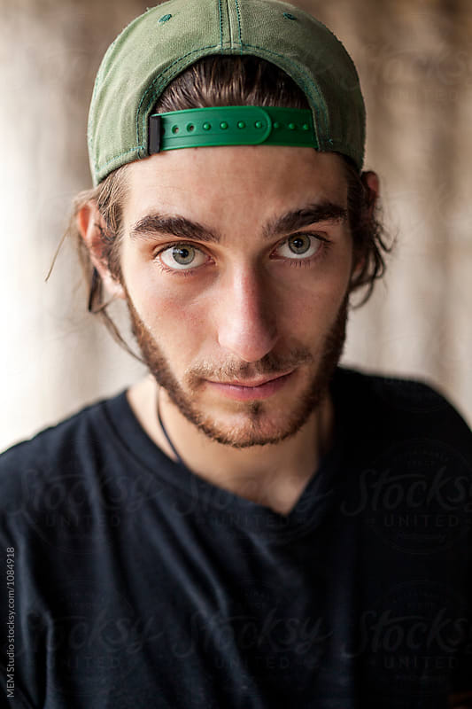 Portrait of a young man with a green hat by MEM Studio for Stocksy United