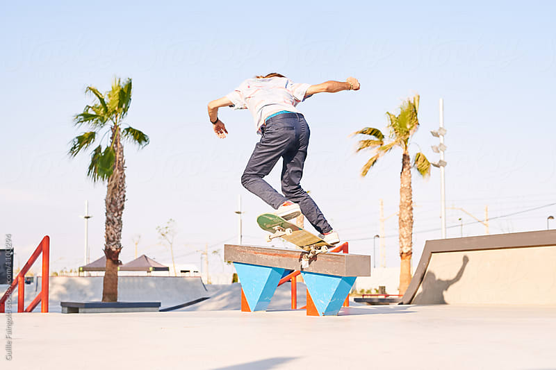 Back view of professional skateboarder performing trick by Guille Faingold for Stocksy United