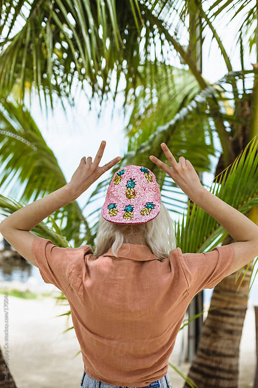 Back of girl giving peace signs on a tropical beach by Image Supply Co for Stocksy United