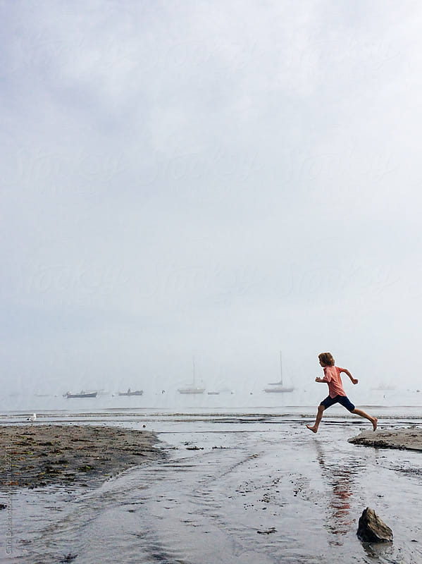 Child runs on a foggy beach in Maine by Cara Slifka for Stocksy United