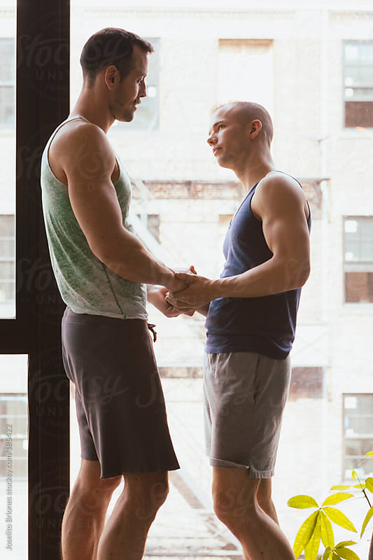 Gay Male Jock Couple Talking and Holding Each Other by Window by Joselito Briones for Stocksy United