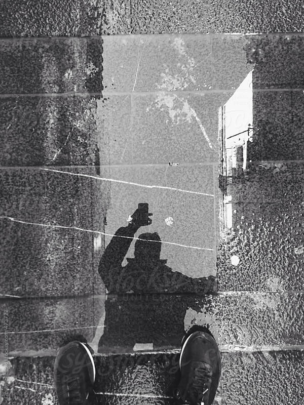 man making a selfie in a puddle by Guille Faingold for Stocksy United