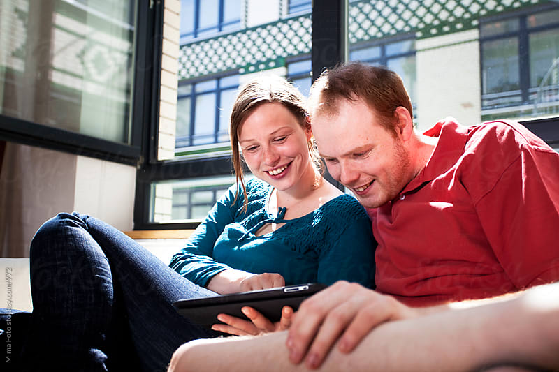 Young couple surfing with tablet computer by Michael Zwahlen for Stocksy United