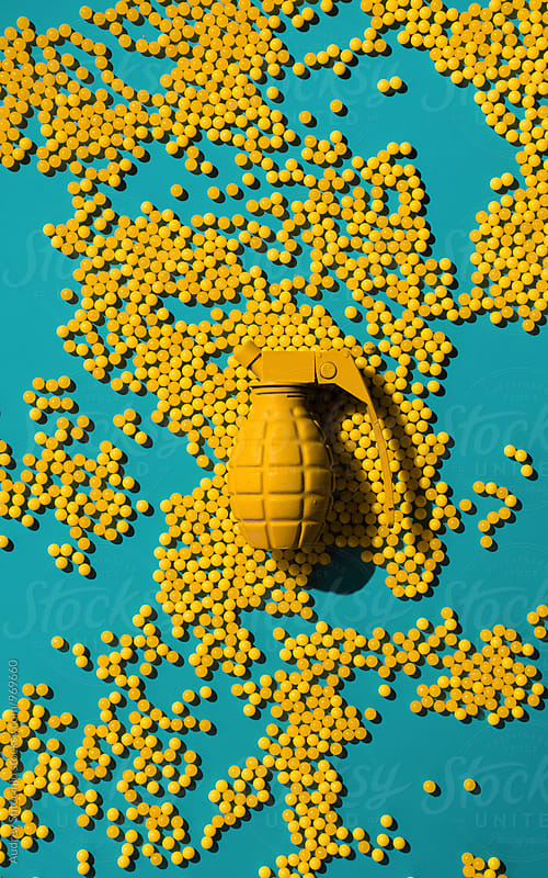 Yellow hand grenade  with yellow shells -ball shaped on blue background . by Marko Milanovic for Stocksy United