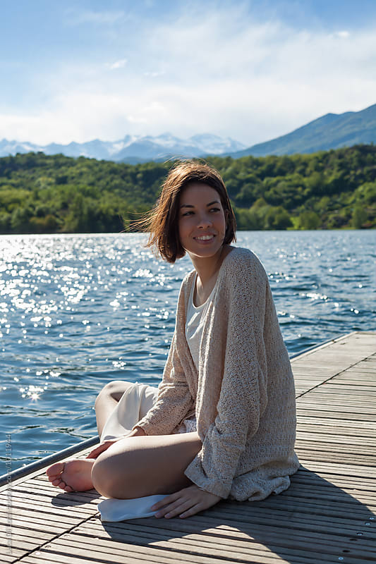 Young beautiful woman sitting by the lake by Luca Di Lotti for Stocksy United