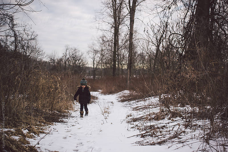 Young Boy Walking on a Snow Covered Hiking Trail  by Kevin Keller for Stocksy United