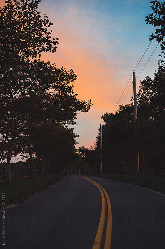 Winding road at sunset by Lauren Naefe for Stocksy United