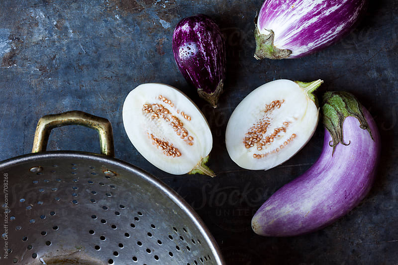 Sliced white and purple aubergine with colander by Nadine Greeff for Stocksy United