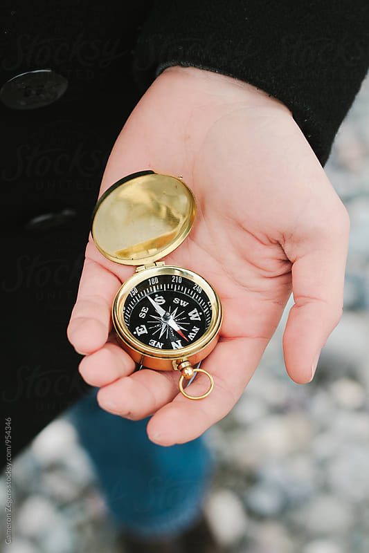 hand holding compass at beach by Cameron Zegers for Stocksy United