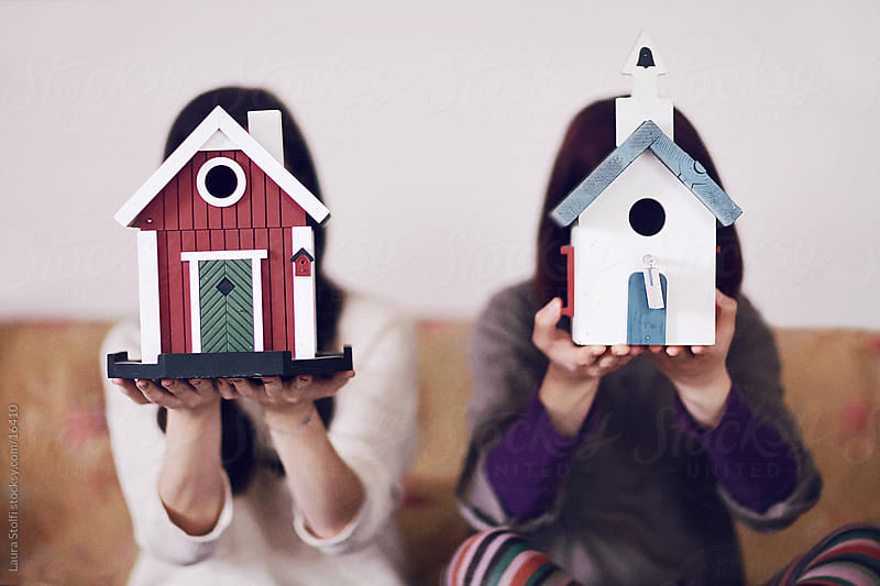 Two young girls sitting on bed and hiding their face behind old house shaped wooden bird houses by Laura Stolfi for Stocksy United