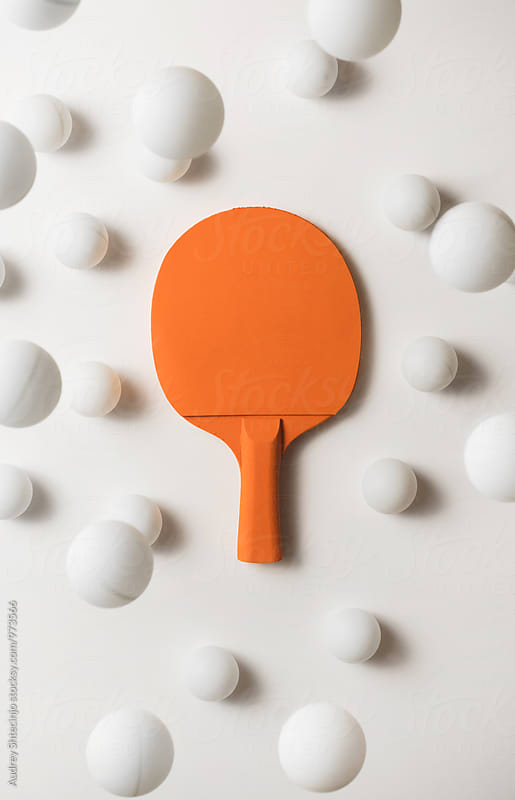 Orange pIng pong racket and white balls flying by Marko Milanovic for Stocksy United