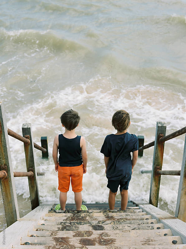 Rear view of two boys on steps looking at the sea by Kirstin Mckee for Stocksy United