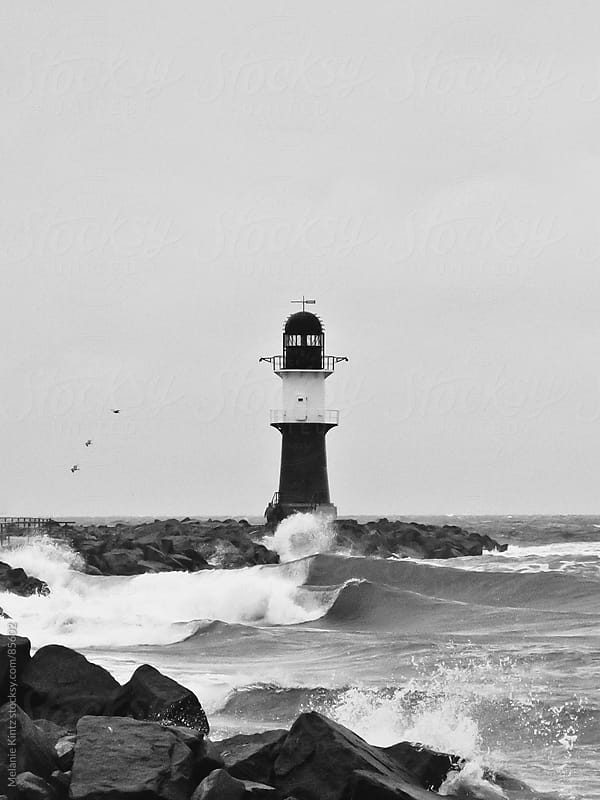 lighthouse at storm with waves crashing, black and white by Melanie Kintz for Stocksy United