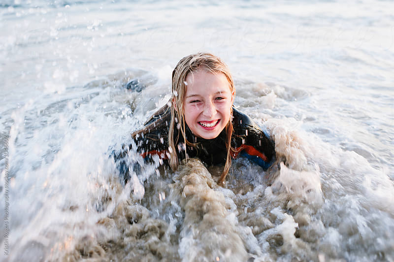 Young girl smiling while in waves at beach by Kristin Rogers Photography for Stocksy United