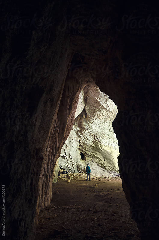 Cave entrance with man standing by Cosma Andrei for Stocksy United