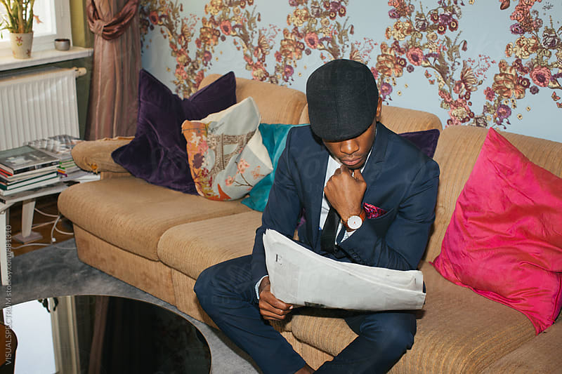 Stylish Young Black Man Reading Newspaper in Colorful Living Room by Julien L. Balmer for Stocksy United