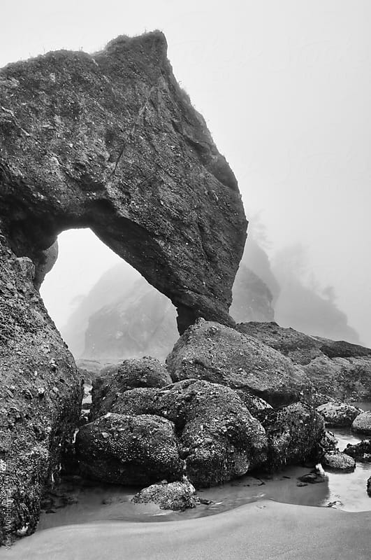 Sea stack arch in fog, black and white by Mark Windom for Stocksy United