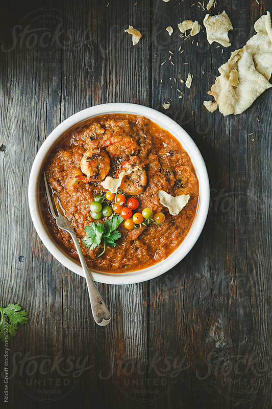 Prawn Curry with tomato garam masala yoghurt gravy and poppadoms by Nadine Greeff for Stocksy United