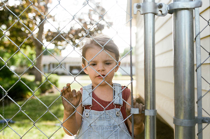 little girl looking through fence by Maria Manco for Stocksy United