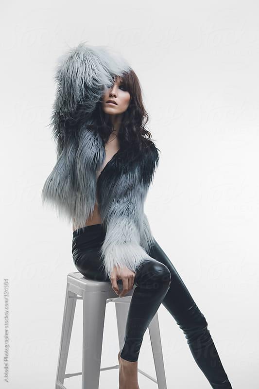 A model posing on a white stool wearing a fur jacket by Ania Boniecka for Stocksy United