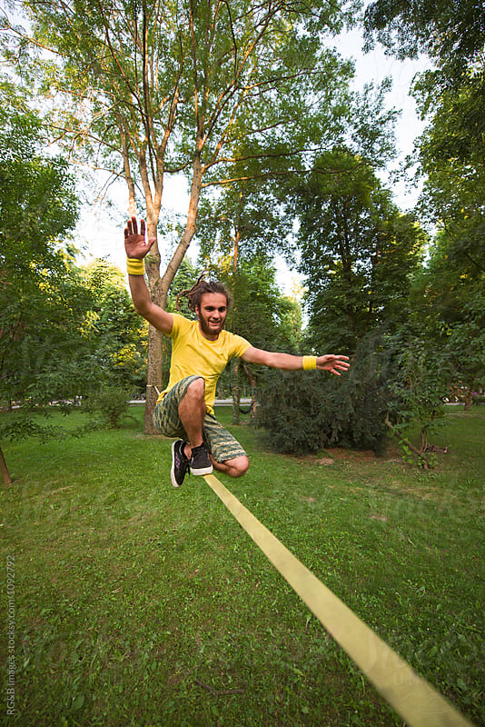 Hipster doing tricks on a slackline in the park by RG&B Images for Stocksy United