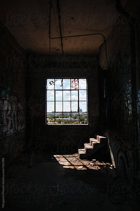 window and stairs in abandoned factory by Margaret Vincent for Stocksy United