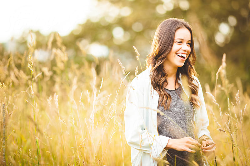 Girl laughing in long grass field on a summer evening by Christian Tisdale for Stocksy United