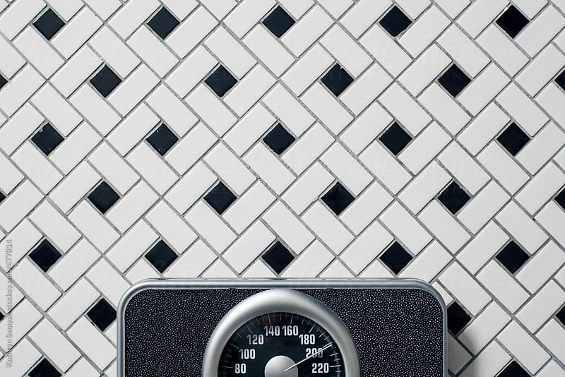 A bathroom scale found on a tiled floor by Kathryn Swayze for Stocksy United