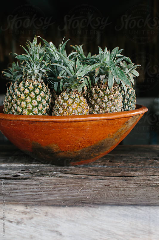 large bowl of pineapples by Cameron Zegers for Stocksy United