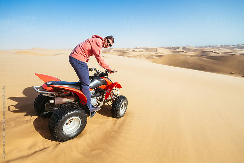 Young man on quad bike in desert by Alejandro Moreno de Carlos for Stocksy United