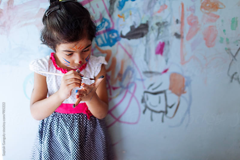 Little girl painting her hand with watercolor by Saptak Ganguly for Stocksy United