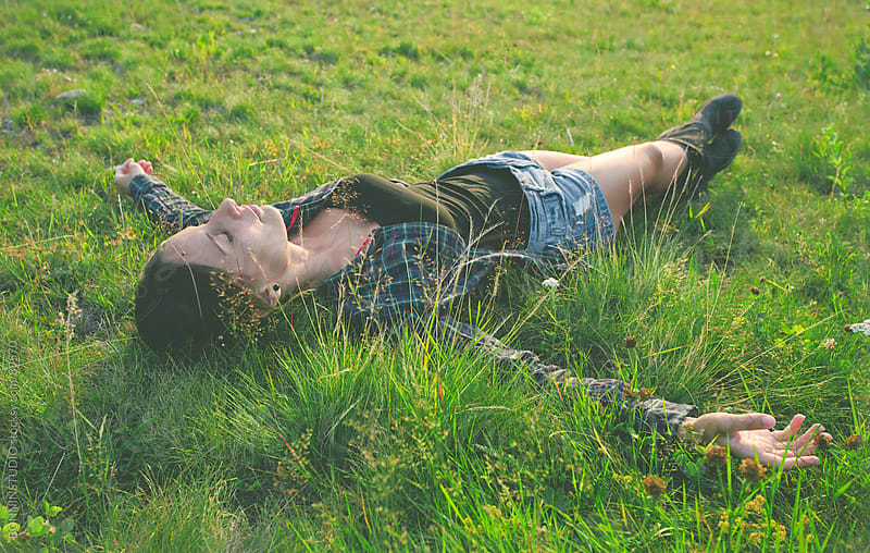 Woman lying on green grass with stretched arms and legs. by BONNINSTUDIO for Stocksy United