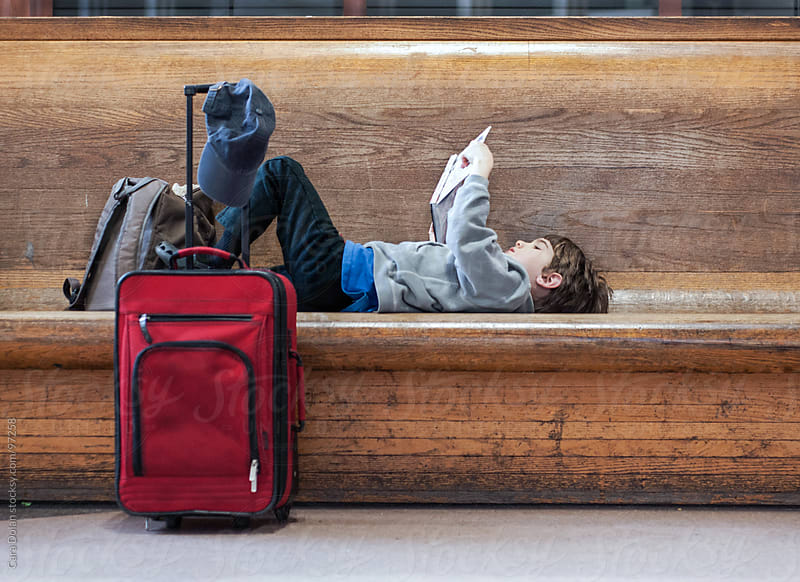 Boy with a suitcase reads a book while lying on a bench at a train station.  by Cara Dolan for Stocksy United